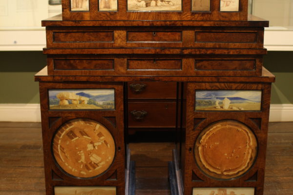 Georgian cabinet in a 'trilithin' shpae with watercolour painting set into the drawers