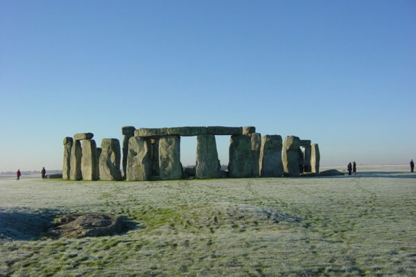 Stonehenge against a clear blue sky with the Slaughter stone in the foreground