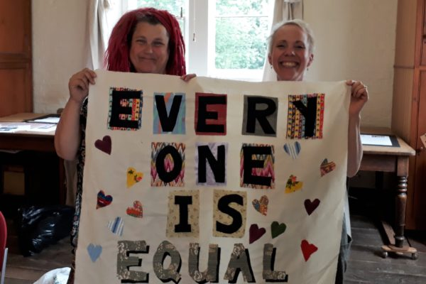 Two ladies holding a hand-made banner saying 'Everyhone is Equal'