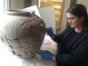 Conservator cleaning the large pottery vessel that held the Cunetion hoard.