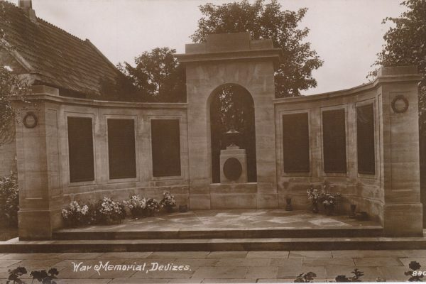 Devizes War Memorial - semim-circle of plaques with names of those who gave their lives with vases of flowers below.