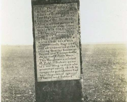 A tall stone with a plague, detailing the events of a robbery