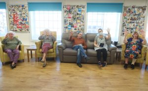 A group of 5 people sitting in chairs. One is wearing a mask and holding up an ipad.