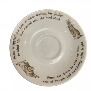 A plate with writing and two images of Peter Rabbit on it